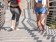 Two young women accidentally meeting while jogging in the city