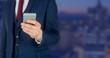Businessman holding phone against Night city