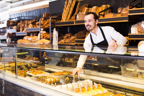 Male shop assistant demonstrating fresh delicious pastry in bakery