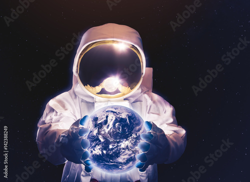 Astronaut in space holding the earth on his hands (Elements of this image were furnished by NASA)