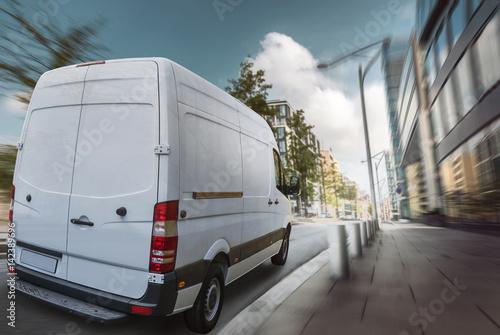 Fotografiet  Lieferwagen fährt am Tag durch eine Stadt