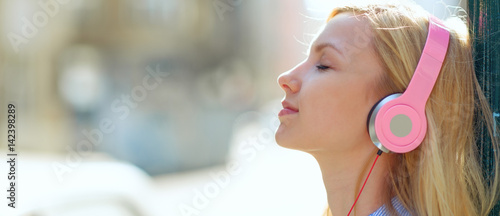 Young woman listening music in headphones in the city - 142398289
