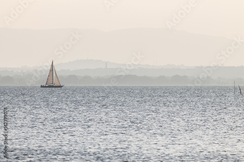 A small sailboat on a lake, with distant hills in the