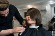 Male hairdresser is preparing for haircut of Beautiful woman in the beauty salon.