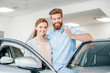 Happy couple holding car key and standing at car in dealership salon