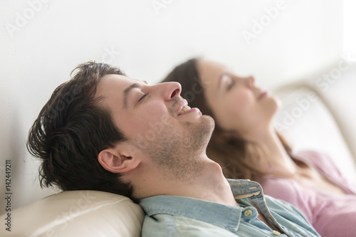 Wall Murals Equestrian Side view of happy young couple enjoying lying on sofa at home, relaxing with eyes closed, recreating, dreaming of vacation, meditating and resting, listening to music, imagining, leisure lazy day