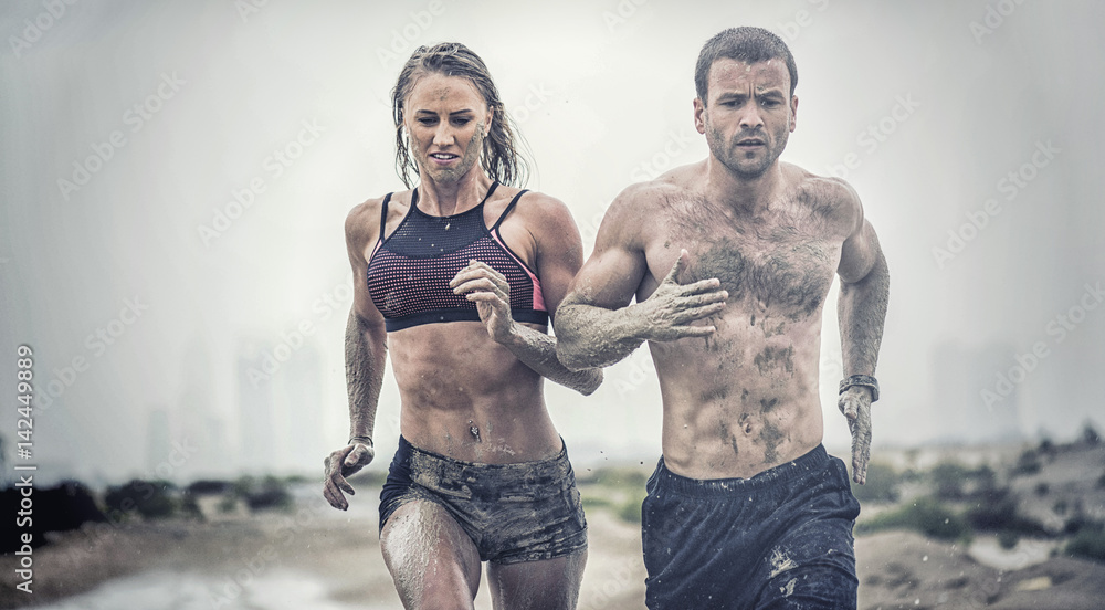 Fototapety, obrazy: Muscular male and female athlete covered in mud running down a rough terrain with a desert background in an extreme sport race