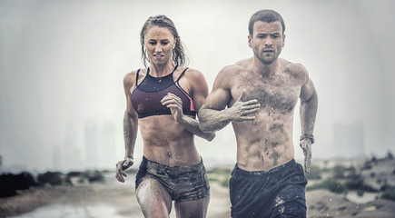 Muscular male and female athlete covered in mud running down a rough terrain with a desert background in an extreme sport race