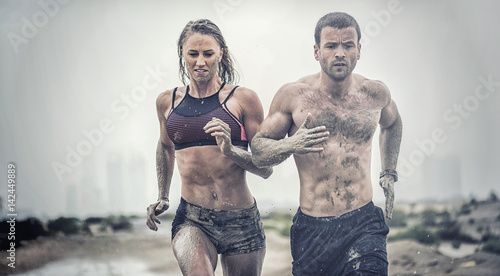 Muscular male and female athlete covered in mud running down a rough terrain with a desert background in an extreme sport race  - 142449889
