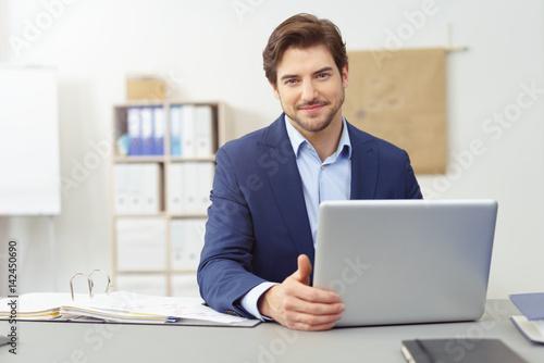 Fotografía  seriöser berater sitzt am schreibtisch und arbeitet am notebook