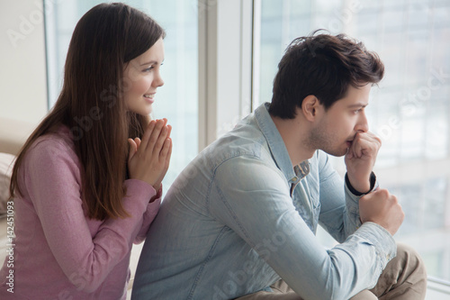 Photo Young woman apologizing upset frustrated man at home