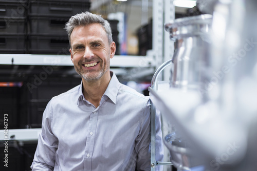 Portrait of smiling businessman in factory hall