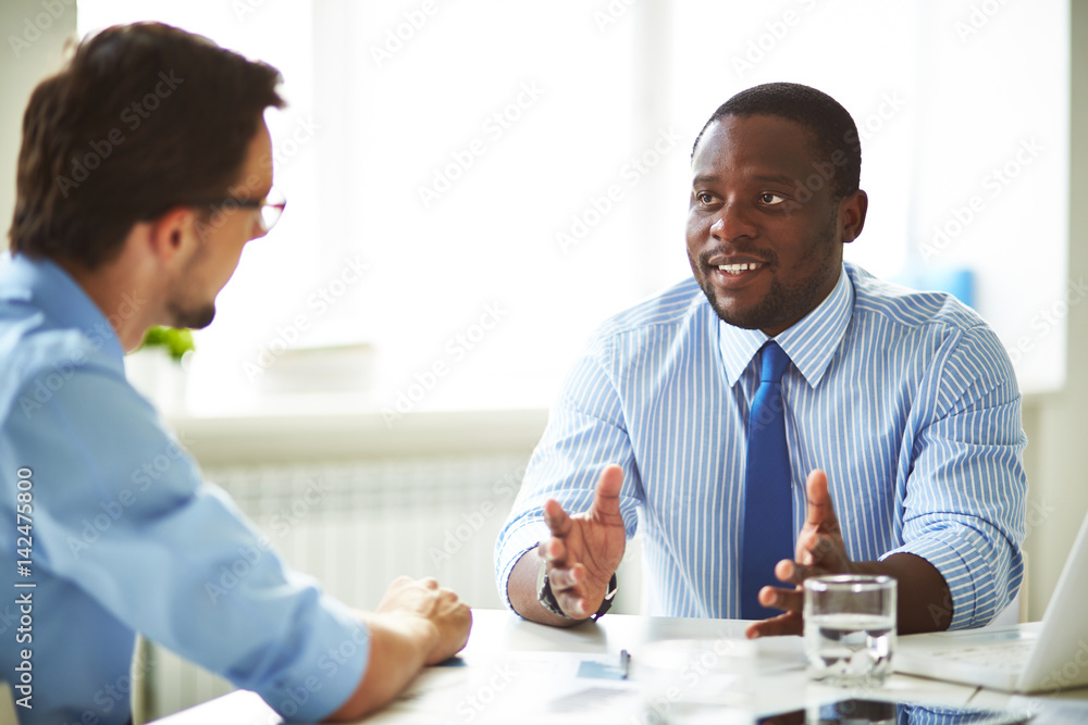 Fototapeta Afro-American bearded HR manager sitting at office desk while conducting interview with male applicant for position