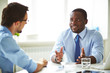 Afro-American bearded HR manager sitting at office desk while conducting interview with male applicant for position