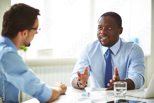 Fotografía  Afro-American bearded HR manager sitting at office desk while conducting intervi