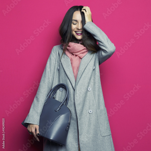 Young stylish woman in grey coat Wall mural