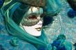 Frau mit Maske und grünem Schleier beim Karneval in Venedig