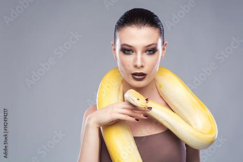 Fotografie, Obraz  Beautiful brunette woman with a albine python