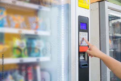 Obraz Female Hand Push Button to make Transaction Code or Number on Modern Automatic Vending Machine - fototapety do salonu
