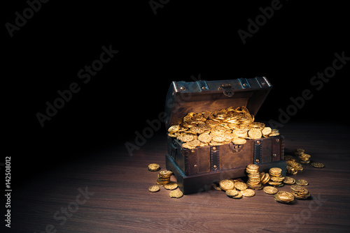 Open treasure chest with gold coins on a dark background Wallpaper Mural