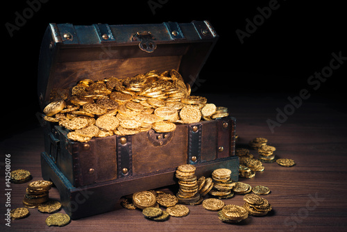 Open treasure chest with gold coins on a dark background Canvas Print