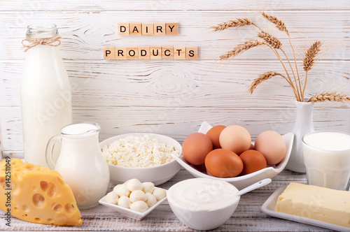 Staande foto Zuivelproducten Dairy products on wooden table. Milk, sour cream, cheese, egg, yogurt and butter. Healthy food, diet concept. Copy space