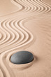 Zen background with stone and pattern of lines in the sand. Focus on concentration and spirituality for harmony and purity. Spa wellness therapy or yoga theme...