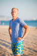 Guy with white hair dressed in shorts stands on the beach near the sea