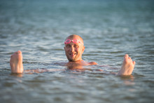 Man With A Bald Head Floating In A Glassy Water Of Dead Sea With Bathing Goggles His Forehead