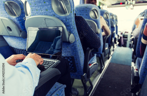 man with smartphone and laptop in travel bus