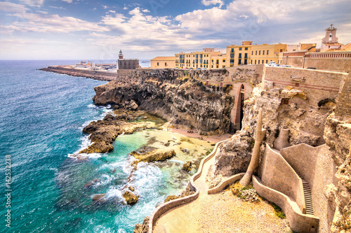 City walls, lighthouse and harbor in Melilla, Spanish province in Morocco. The rocky coast of the Mediterranean Sea.