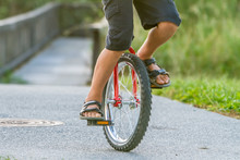 Outdoor Portrait Of Young Boy Riding A Unicycle On Natural Background