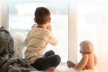Cute Little Boy With Teddy Bear Sitting On Window Sill At Home