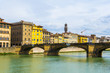 Historical buildings stretched alongside river Arno in the historical center of the italian city Florence near bridge ponte santa trinita