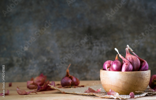 the shallots in bowl on old wooden table with old wallpaper background