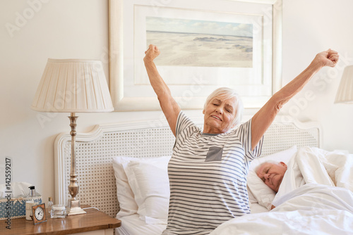 Fototapeta  Senior woman waking up with a stretch in the morning