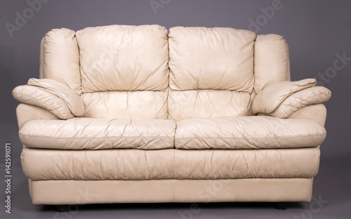 Valokuvatapetti A grubby two seater cream colored leather sofa