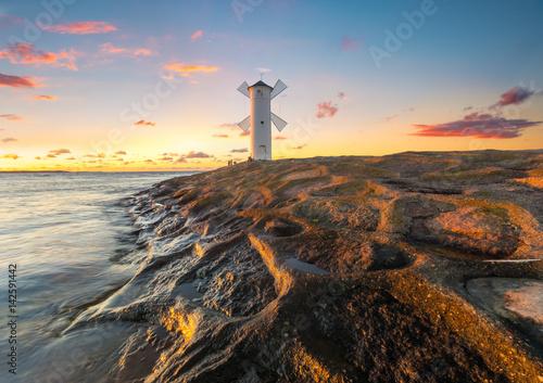 Obraz Beautiful sunset over a windmill-shaped lighthouse, Swinoujscie, Poland. - fototapety do salonu
