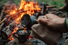 Making Coffee Process On The Campfire. Man Pour Coffe In Potter Cup
