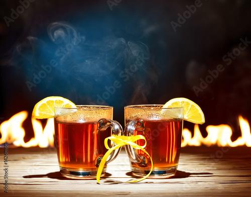 Obraz na płótnie Two mugs with black tea, lemon against the fireplace