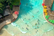 Top View Of Water Park With Many Traveler Have Fun Swimming Pool In Sentosa, Singapore.