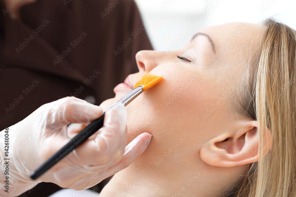 Fototapeta Pielęgnacja skóry, kosmetyczka nakłada pędzelkiem maseczkę na twarz kobiety