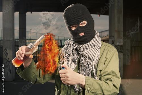 Anarchist in balaclava lighting molotov cocktail glass bomb Canvas Print