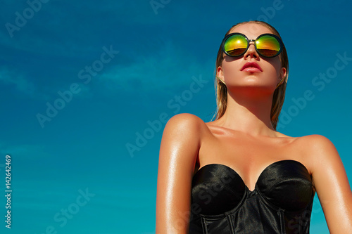 Foto Fashionable girl with a beautiful tan is against the blue clear sky