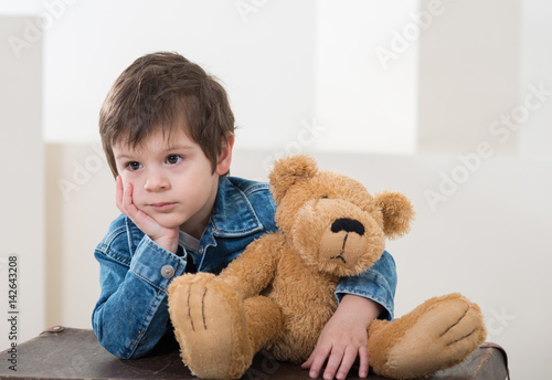 Little boy sitting on the travel retro brown suitcases in  jeans jacket with a bear #142643208