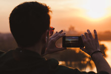 Young Man Taking A Picture Of The Sunset On His Smartphone