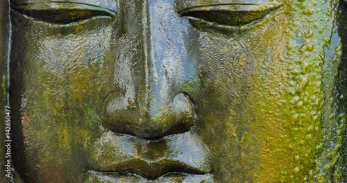 Water flows over sacred Buddhist statue of Buddha face as example of ancient arc Canvas Print