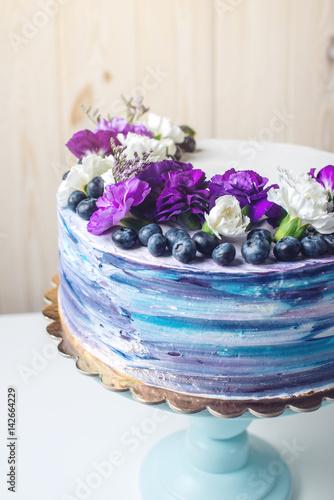 Zdjęcie XXL Kolorowy ślubny tort z uroczymi purpurowymi kwiatami i czarnymi jagodami