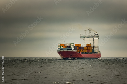 Spoed Foto op Canvas Khaki Red cargo container ship sailing from Baltic sea in cloudy day