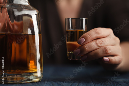Poster Bar woman drinking alcohol on dark background. Focus on wine glass